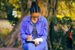 Woman writing a book in a park
